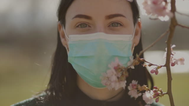 vídeos de stock e filmes b-roll de attractive sad young woman with green eyes wears surgical face mask and looks at you. slow motion shot with sakura blossom at blurry background during coronavirus pandemic - máscara cirúrgica