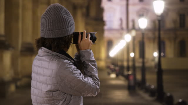 vidéos et rushes de attractive smiling black female takes photo of french museum at night - musée