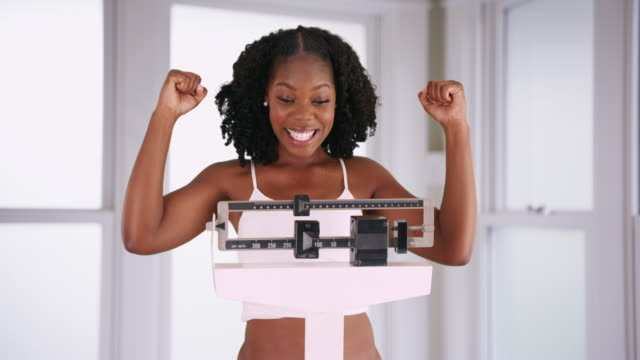 attractive smiling black woman cheers at weight loss pointing at scale happily - weight scale stock videos & royalty-free footage