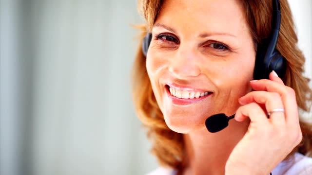 attraktive lächelnd call-center-mitarbeiter - sekretärin stock-videos und b-roll-filmmaterial