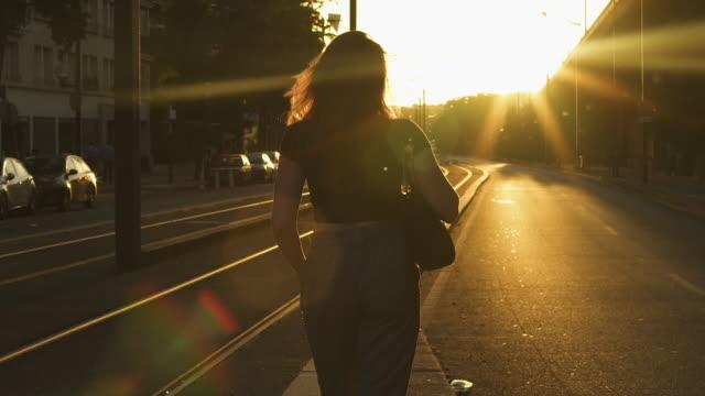 vídeos de stock, filmes e b-roll de mulher pensativa atrativa do redhead com óculos de sol, freckles, perfurações e cabelo vermelho que levantam após o trabalho em trilhos do bonde, durante a noite ensolarada do verão em paris. câmara lenta. hora dourada. vista de trás. - bonde