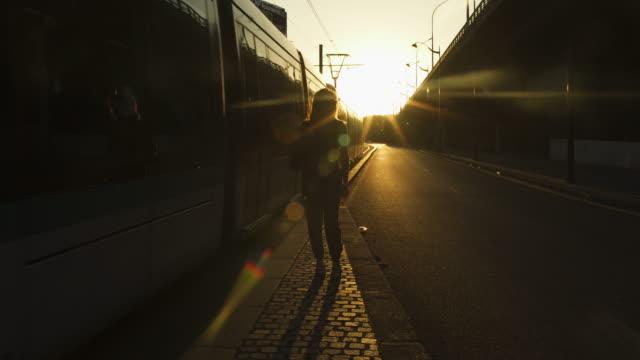vidéos et rushes de femme réfléchie attirante de rousse avec des lunettes de soleil, des taches de rousseur, des piercings et des cheveux roux posant après le travail sur des rails de tram, pendant la soirée ensoleillée d'été à paris. heure d'or. tir large. tram de pa - tramway