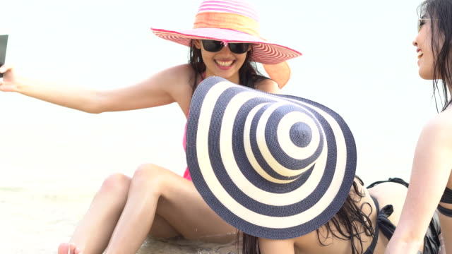 attractive three woman enjoys in hat on the beach - straw hat stock videos and b-roll footage