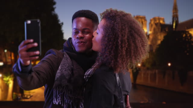 attractive tourist couple pose for a selfie near notre dame cathedral at night - baciare video stock e b–roll
