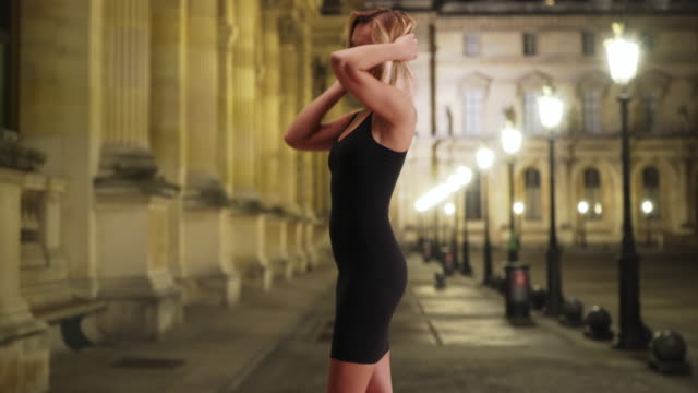 attractive white lady in dress moving sensually near european building at night - black dress stock videos & royalty-free footage
