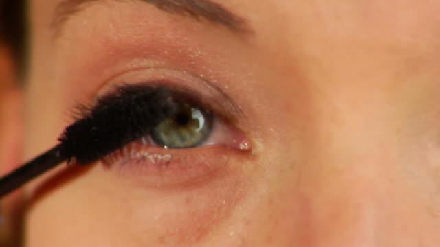 vídeos de stock, filmes e b-roll de bela mulher aplicar rímel - olhos verdes