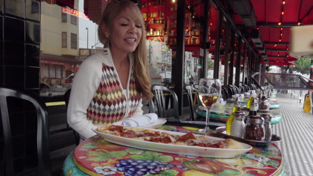 attractive woman being served a pizza at an outdoor restaurant. - italian food stock videos and b-roll footage