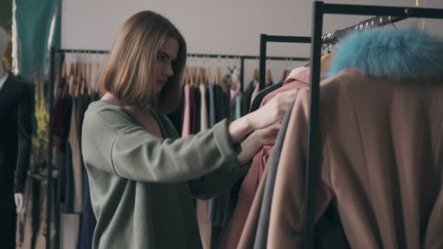 attractive woman choosing stylish coat in store - boutique stock videos & royalty-free footage