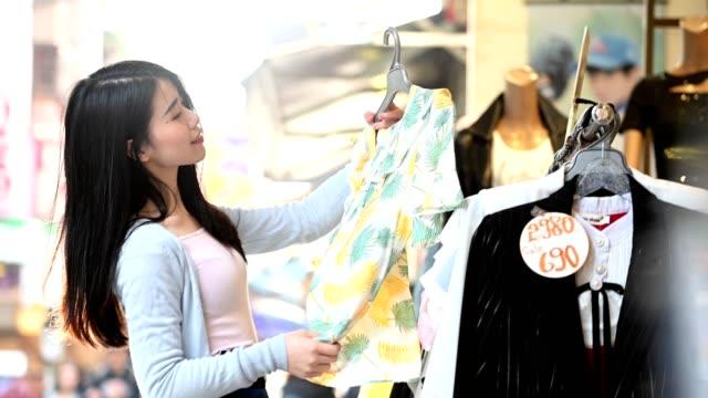 stockvideo's en b-roll-footage met aantrekkelijke vrouw kiezen top bij kledingwinkel - driekwartlengte