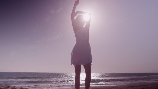 attractive woman dancing at the beach in white dress - 白のドレス点の映像素材/bロール