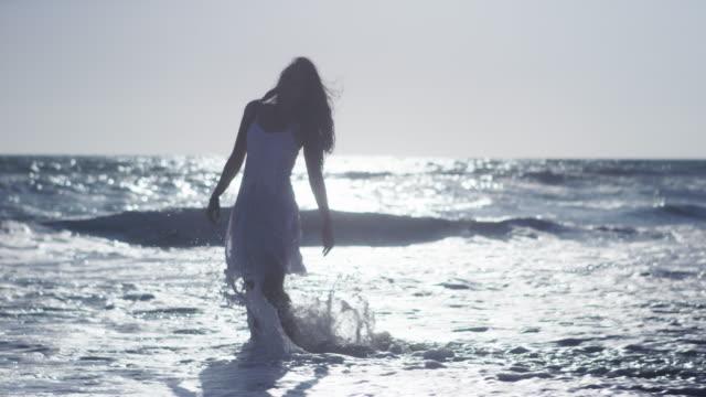 vídeos de stock e filmes b-roll de attractive woman dancing at the beach in white dress - vestido branco