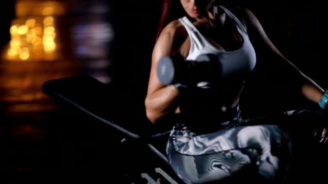 stockvideo's en b-roll-footage met aantrekkelijke vrouw doet biceps oefeningen zittend op de bank en het verhogen van halter in de sportschool - bicep