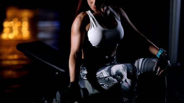 vidéos et rushes de femme attirante faisant des exercices de biceps tout en s'asseyant sur le banc et élevant l'haltère dans la salle de gym - quête de beauté