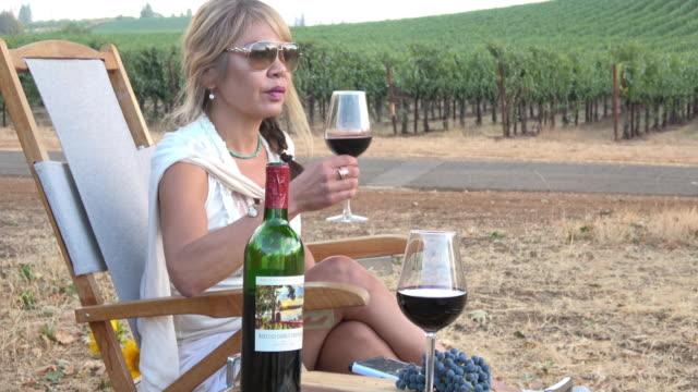 vídeos y material grabado en eventos de stock de mujer atractiva bebiendo una copa de vino en un viñedo de picnic - uva cabernet sauvignon