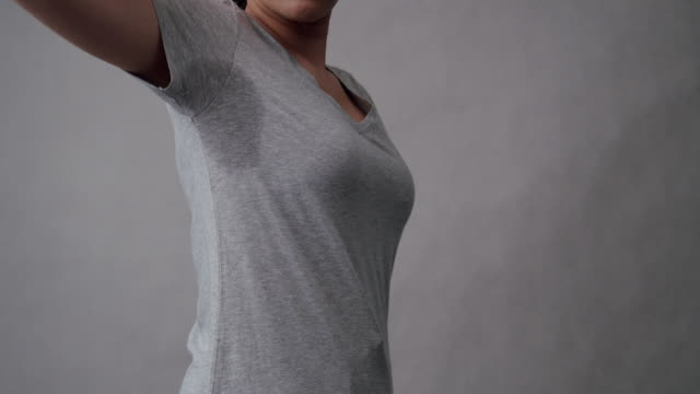 vídeos de stock e filmes b-roll de attractive woman embarrassing on her sweat stain on her gray t-shirt.asian female nasty smell from sweat on her armpit with gray background.healthcare and hyperhidrosis or excessive sweating concepts - manchado sujo