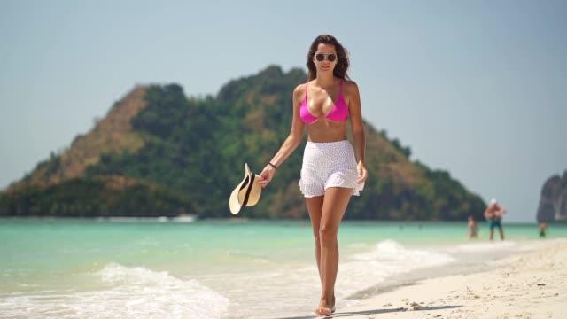 donna attraente che si gode sulla spiaggia - occhiali da vista video stock e b–roll