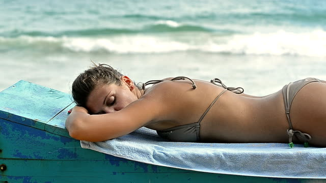 Attractive woman enjoys summer sunbathing on coast of Indian Ocean in Sri Lanka