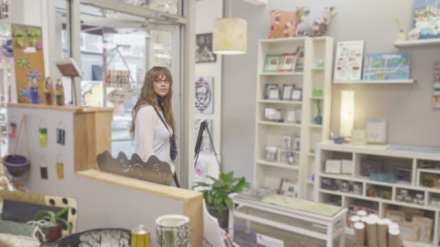 魅力的な女性の衣料品店に入る - ギフトショップ点の映像素材/bロール