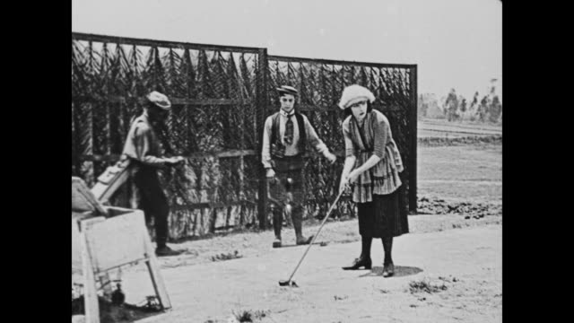 vídeos de stock, filmes e b-roll de 1920 attractive woman (sybil seely) hits a good golf drive - bolsa de golfe