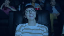 Attractive woman in glasses laughing having fun in cinema with group of people