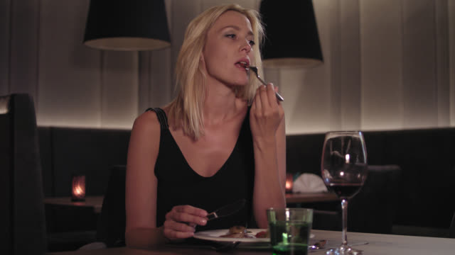 attractive woman in her 30s with long blonde hair in black dress sits at a table in a stylish hotel restaurant in front of a plate with her first course and a glass of red wine, she is eating and drinking while waiting for her delayed date to arrive. - gutes benehmen stock-videos und b-roll-filmmaterial