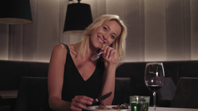 vídeos de stock e filmes b-roll de attractive woman in her 30s with long blonde hair in black dress sits at a table in a stylish hotel restaurant in front of a plate with her first course and a glass of red wine, she is eating and drinking before she looks into the camera with a big smile. - vestido preto