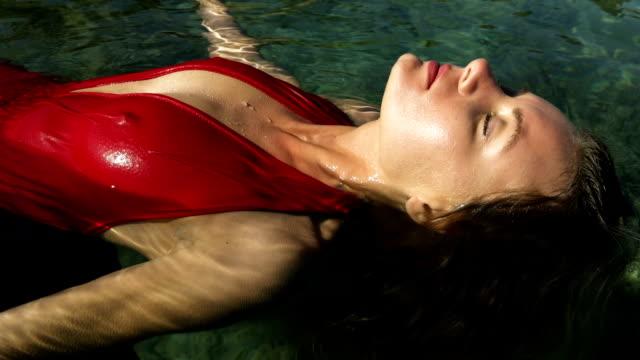 attractive woman in red dress floating on sea - galleggiare sull'acqua video stock e b–roll