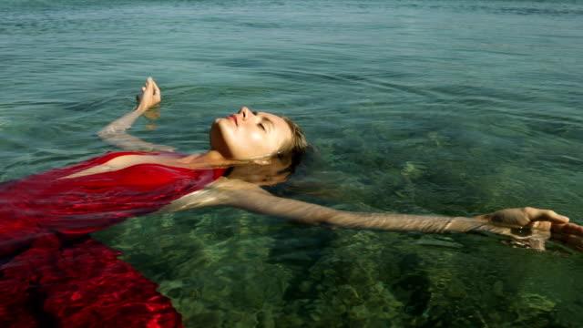 Aantrekkelijke vrouw in rode jurk drijvend op de zee