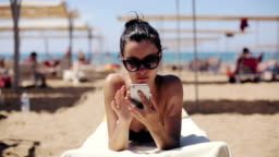 Attractive woman in sunglasses relaxing and using app on smartphone