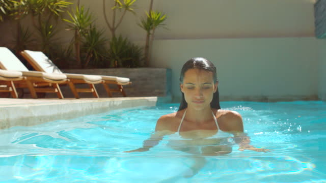attractive woman in swimming pool walking toward the camera - freibad stock-videos und b-roll-filmmaterial