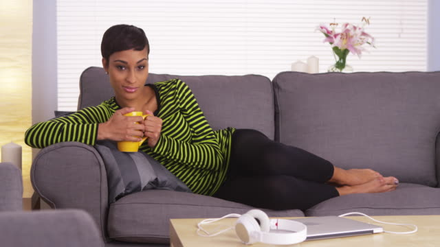 attractive woman lying on couch looking at camera - puerto rican ethnicity stock videos & royalty-free footage