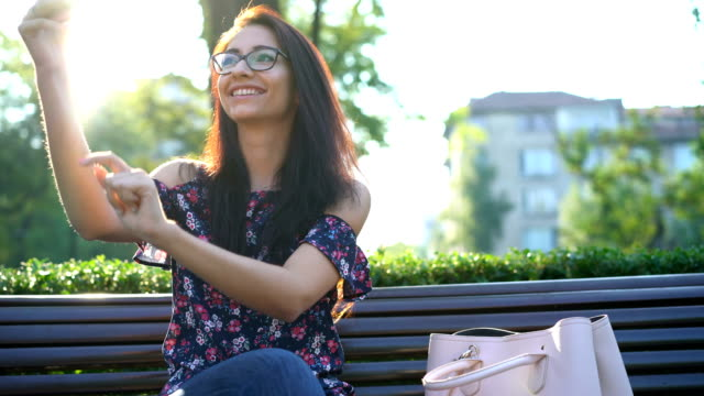 attractive woman making selfies with her phone in the park - kissing hand stock videos & royalty-free footage