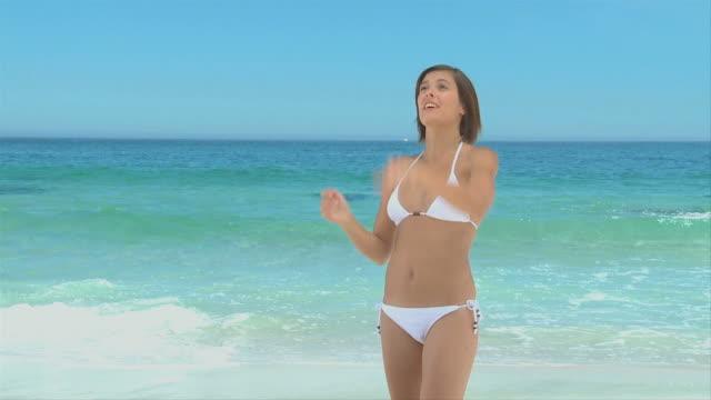 vídeos de stock, filmes e b-roll de attractive woman playing with a beach ball / cape town, western cape, south africa - biquíni