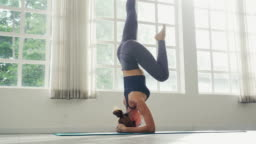 Attractive woman practicing yoga with beautiful headstand pose