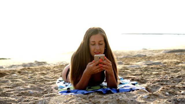 donna attraente rilassante e utilizzando l'app su cellulare sulla spiaggia soleggiata - super slow motion video stock e b–roll