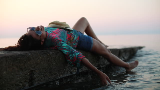 vídeos y material grabado en eventos de stock de mujer atractiva relajante en muelle - accesorio de cabeza