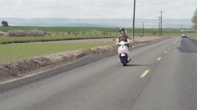 Attraktive Frau Reiten auf Roller auf ländliche Straße
