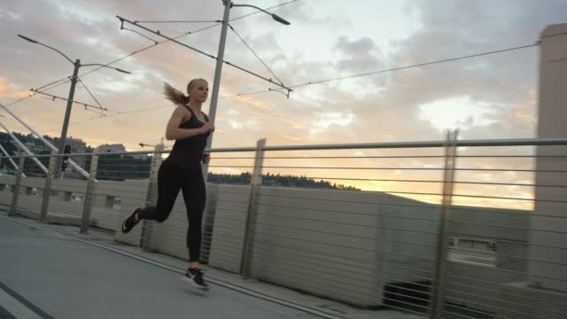 Aantrekkelijke vrouw uitgevoerd in de stad een brug bij zonsondergang