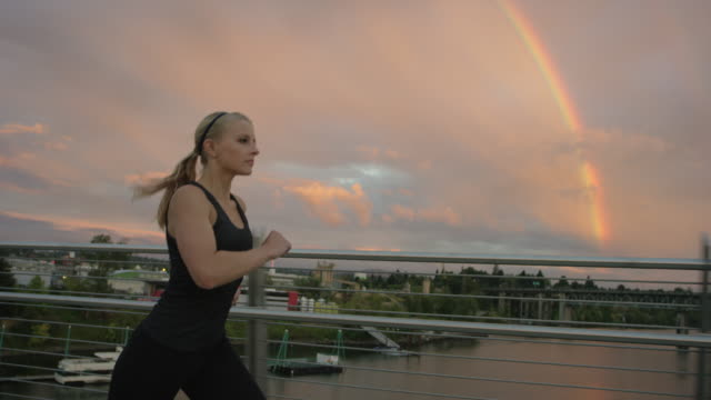 attractive woman running in the city across a bridge at sunset - arcobaleno video stock e b–roll