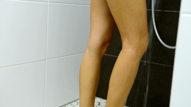Attractive woman showering and massaging her legs