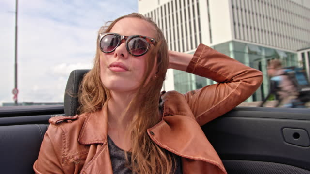 attractive woman sit's in the back of a convertible while driving over a bridge (hackerbrücke - munich) - blondes haar stock-videos und b-roll-filmmaterial