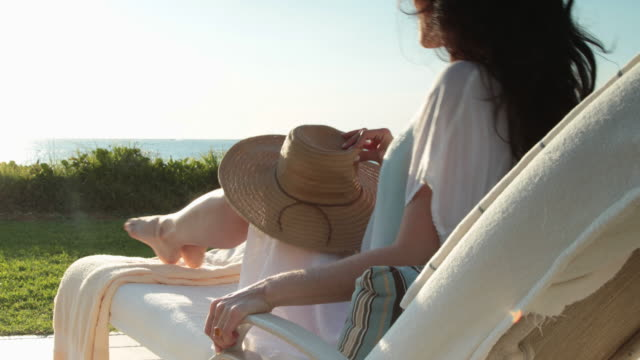 cu attractive woman sits on sun lounger, puts on sun hat and looks out to sea. - sunbathing stock videos & royalty-free footage