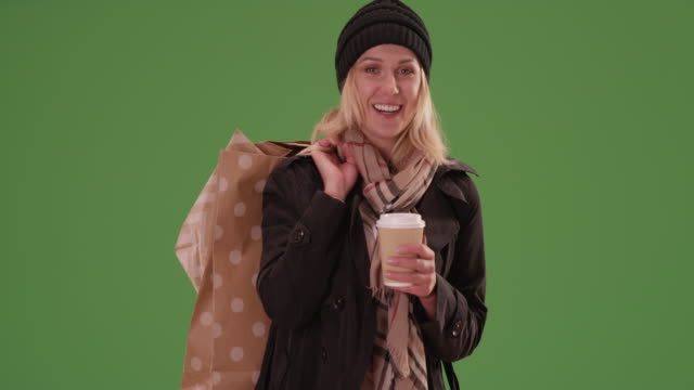 vídeos de stock, filmes e b-roll de attractive woman smiling at camera with shopping bags on green screen. - chapéu