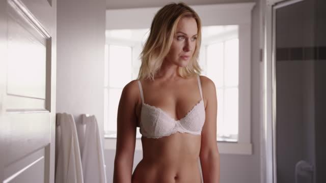 stockvideo's en b-roll-footage met attractive woman standing in bathroom in white underwear - natuurlijk haar