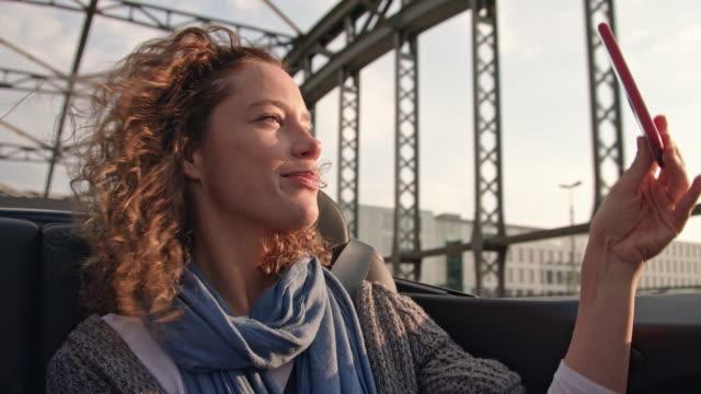 vídeos de stock, filmes e b-roll de attractive woman takes selfies in the back of a convertible while driving over a bridge (hackerbrücke - münchen) - ponto de vista de carro