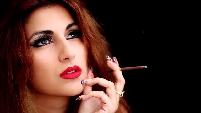 vídeos de stock e filmes b-roll de mulher atraente pensar que fumar um cigarro - questões tabágicas