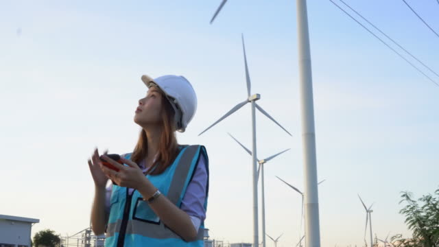 attractive woman using mobile phone at wind farm - turbine stock videos & royalty-free footage