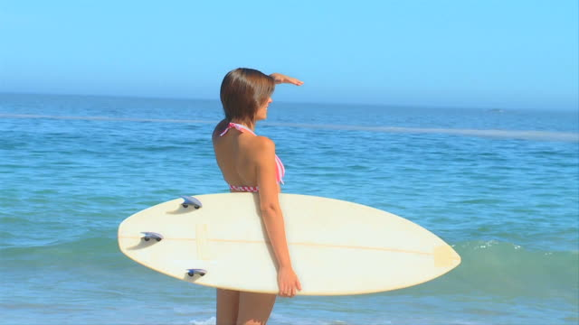 attractive woman waiting to surf / cape town, western cape, south africa - 手をかざす点の映像素材/bロール