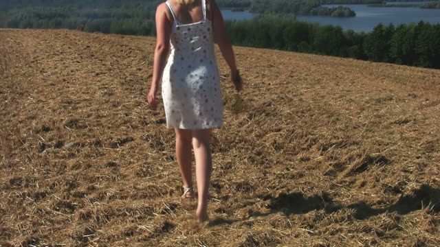 attractive woman walking on the field - mini skirt stock videos and b-roll footage
