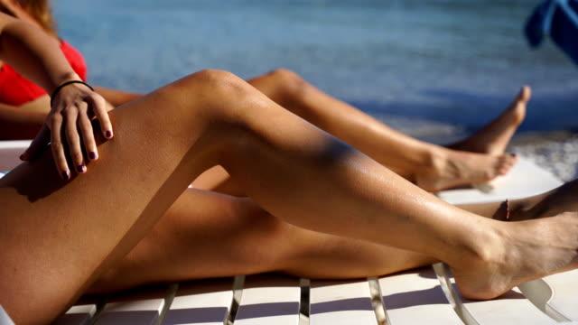 vídeos de stock, filmes e b-roll de mulher atrativa com pele saudável que aplica o protetor solar a seu corpo - bronzeado